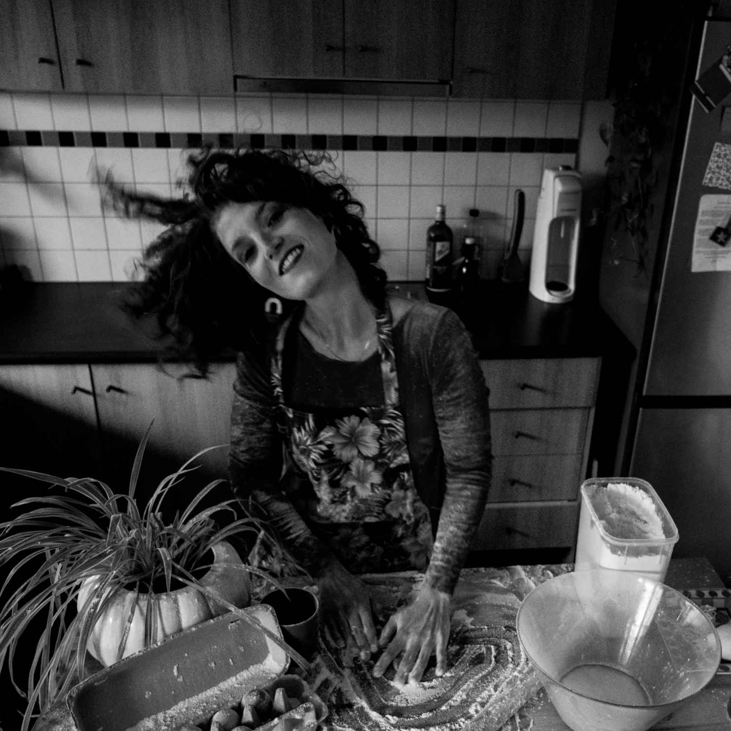 A black and white photo of Xani Kolac dancing in the kitchen
